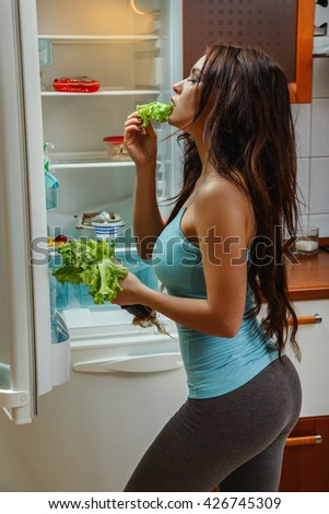 Beautiful girl eats a lettuce leaf in front of the fridge
