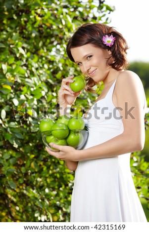 Beautiful girl eats an apple in a summer garden - stock photo