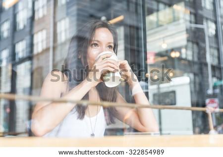 beautiful girl enjoying an hot coffee inside a shop in New york - stock photo