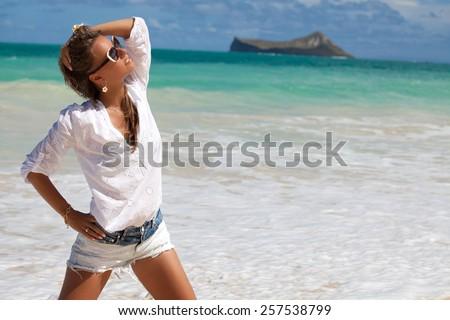 Beautiful girl enjoying the perfect summer day. Beach vacation - carefree woman relaxing on Lanikai beach, Honolulu, Oahu Island, Hawaii, USA  - stock photo