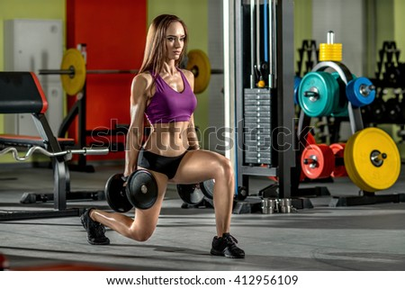 beautiful girl, execute exercise with dumbbells, in dark gym - stock photo