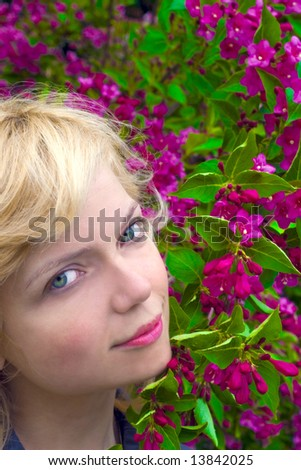 Beautiful girl face arounf the res flowers - stock photo