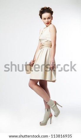 Beautiful girl fashion model in modern clothes posing on podium - series of photos - stock photo