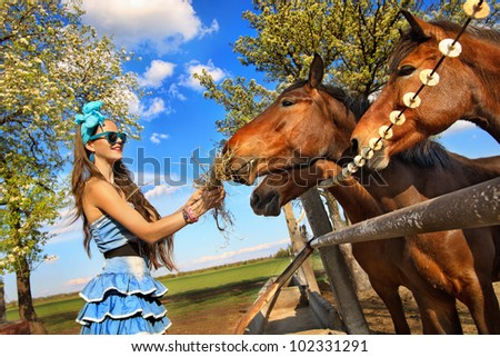 Beautiful girl feeding her horses at ranch