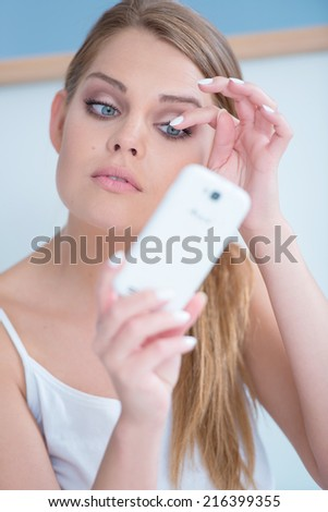 Beautiful girl fixing her eye lashes by using her phone as a mirror - stock photo