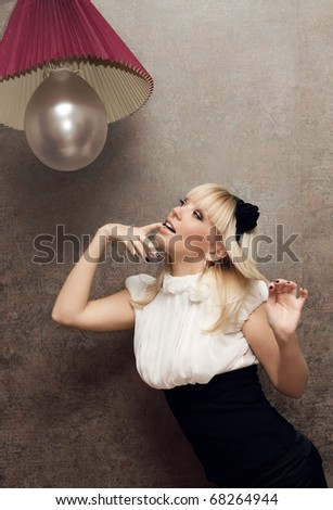 Beautiful girl flirt in the studio under the lamp - stock photo