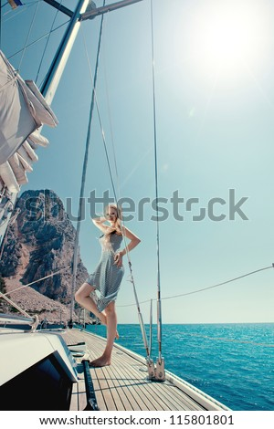 beautiful girl floating in the sea on a boat along the rocky shore - stock photo