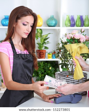 Beautiful girl florist with flowers in flowers shop  - stock photo