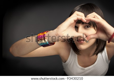 Beautiful girl forming heart with her hands - stock photo