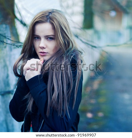 Beautiful girl freezing in the street. Photos in cold tones - stock photo
