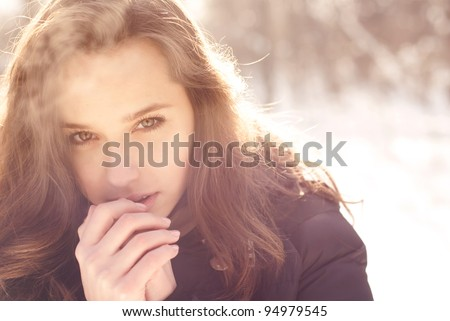 beautiful girl freezing in winter park. pictures in warm colors - stock photo