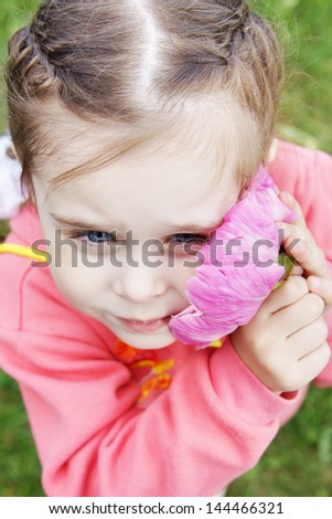 Beautiful girl gently presses to cheek a big pink flower - stock photo