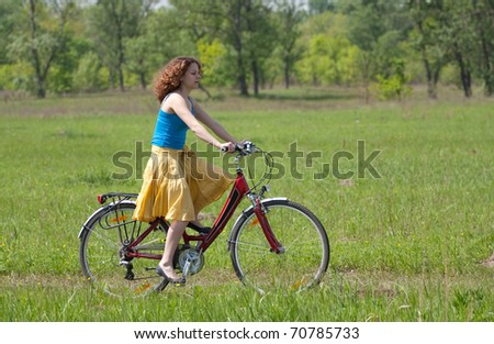 beautiful girl goes by bicycle - stock photo