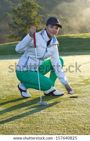 Beautiful girl golf player on field.