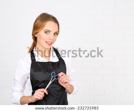 Beautiful girl hairdresser on light background