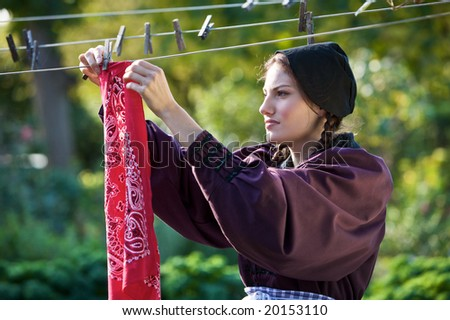 Beautiful girl hanging the laundry outdoors to dry - stock photo