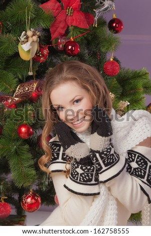 Beautiful girl hanging toy on Christmas tree