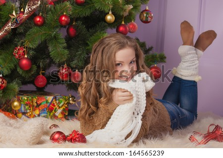 Beautiful girl hanging toy on Christmas tree - stock photo