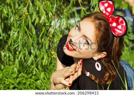 beautiful girl happy smiling in the costume of a mouse with a big red bow down on the grass in the Park - stock photo