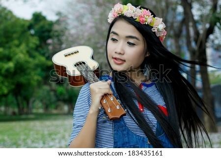 Beautiful girl happy with ukulele guitar under pink flower tree - stock photo