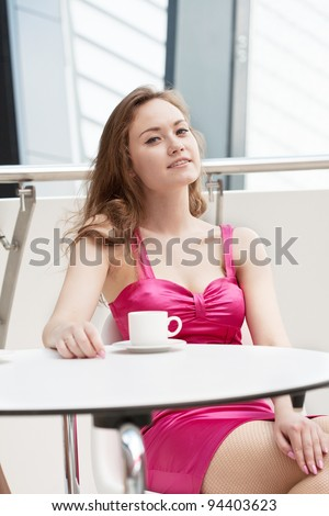 beautiful girl has a rest in cafe in shopping center - stock photo