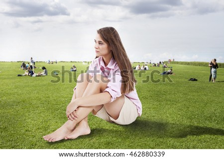 Beautiful girl has a rest on the lawn.
