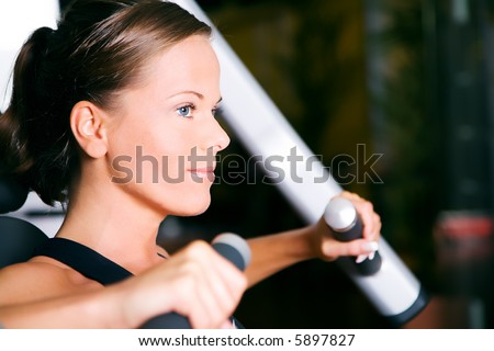 Beautiful girl having a workout in a gym (face in profile) - stock photo