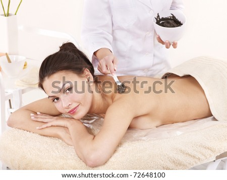 Beautiful girl having clay body mask apply by beautician. - stock photo