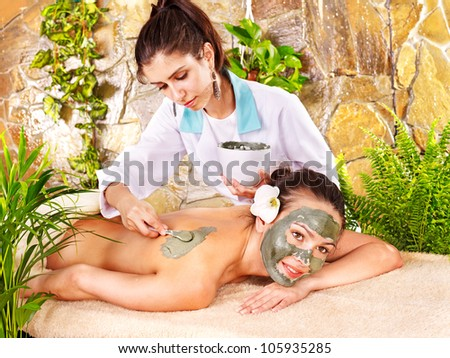 Beautiful girl having clay facial mask apply by beautician. - stock photo