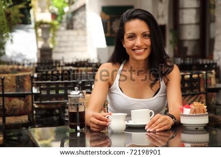 Beautiful girl having coffee in bistro - stock photo