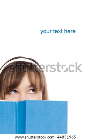 beautiful girl hiding herself behind a book - stock photo