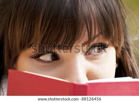 Beautiful girl hiding herself behind a book - stock photo