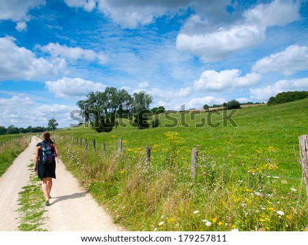 Beautiful girl hiking in a rural landscape in the summer - stock photo