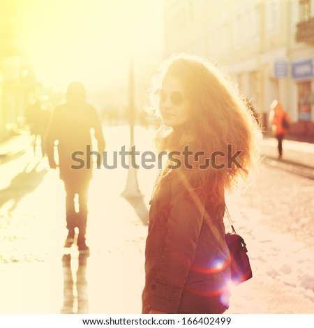 Beautiful girl hipster on the street with a camera in bright sunlight - stock photo