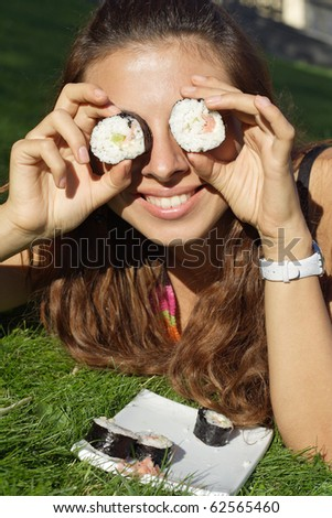 Beautiful girl hold rolls or sushi near eyes funny. More images of this models you can find in my portfolio - stock photo