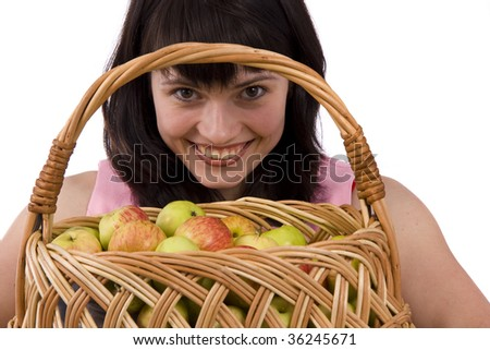 Beautiful girl holding a basket of delicious fresh fruits. Woman in pink dress is standing and holding a basket full apples on white background. Pretty girl with basket of apples.Isolated over white - stock photo