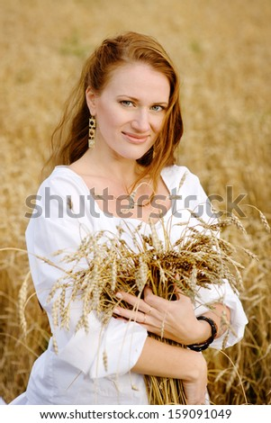 beautiful girl holding a bunch of wheat ears