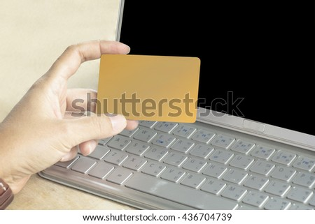 Beautiful girl holding a credit card and typing. Online shopping on the internet using a laptop. Clipping path on card and laptop - stock photo
