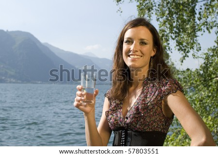 Beautiful girl holding a glass of water at the lake of Zell am See, Austria - stock photo