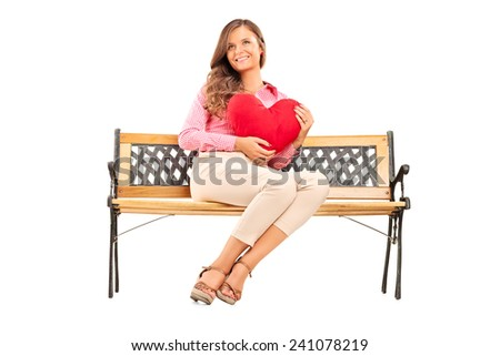 Beautiful girl holding a red heart seated on a wooden bench isolated on white background - stock photo