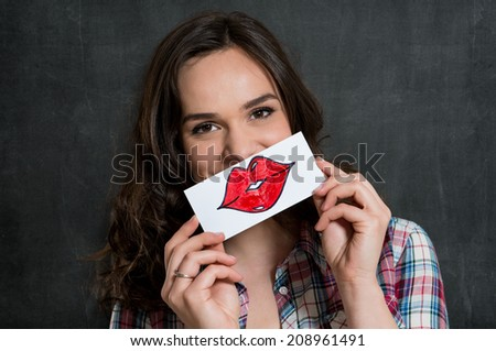 Beautiful Girl Holding A Sheet Of Paper With Drawn Red Lips Isolated On Gray Background - stock photo