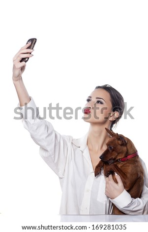 beautiful girl holding a small dog and make themselves self-portrait by phone - stock photo