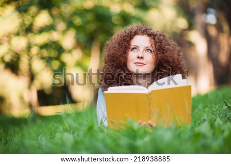 Beautiful girl holding an open book,  summer green park background. - stock photo
