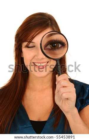 Beautiful girl holding magnifying glass showing big eye - stock photo
