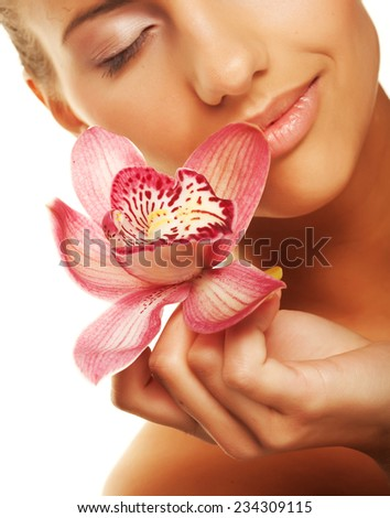 Beautiful girl holding orchid flower in her hands - stock photo