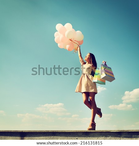 Beautiful girl holding shopping bags and colored balloons over blue sky, toned - stock photo