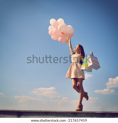 Beautiful girl holding shopping bags and colored balloons over blue sky, toned. - stock photo