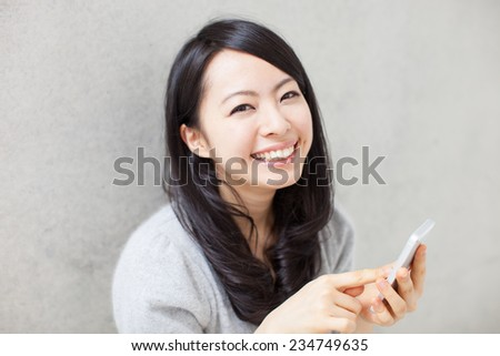 beautiful girl holding smart phone against concrete wall - stock photo