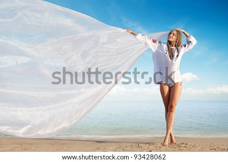 Beautiful girl holding white cloth against blue sky - stock photo