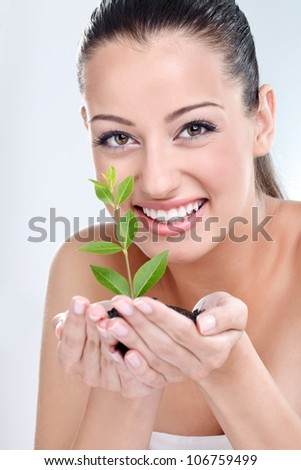 Beautiful girl holding young plant in her hand - stock photo